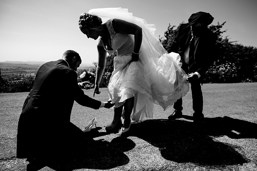 bride putting on wellington boots for her couple's portrait in black and white