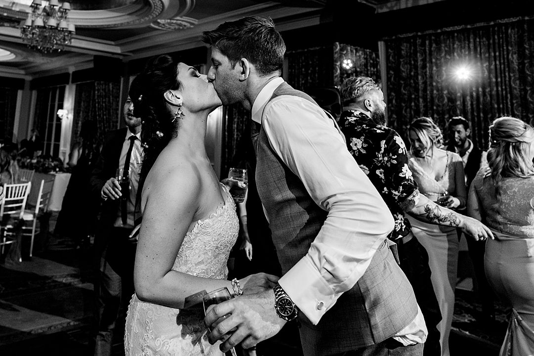 bride and groom kissing on dance floor at RAC Woodcote Park