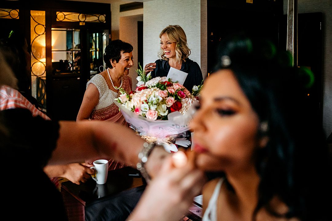 Syon Park Wedding Photography bride getting makeup on as bride's mum and bridesmaid are laughing